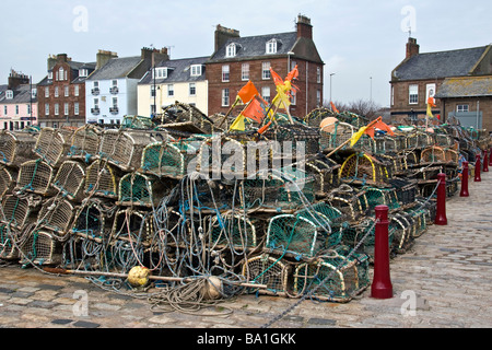 Fishing creels alongside Arbroath harbour and at the quay side and row of colourful harbour houses UK - Stock Photo