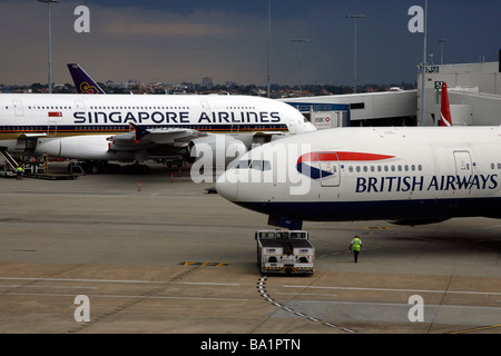 A British Airways Boeing 777-200 aircraft passes an Airbus A380 plane at Sydney Kingsford Smith International Airport - Stock Photo
