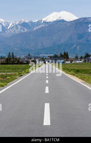 Empty Road Leading To Houses in Northern Alps, Hokkaido - Stock Photo