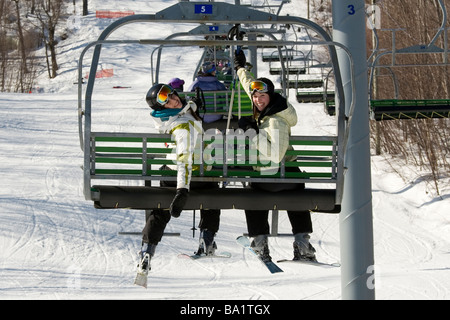 Two sisters on chair lift going skiing - Stock Photo