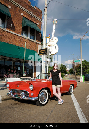 Female model standing beside a 1956 Ford Thunderbird parked in front of Sun Recording Studios in Memphis TN Home - Stock Photo