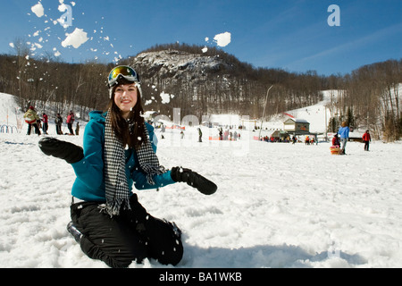 Young girl playing in snow at bottom of ski hill - Stock Photo