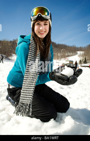 Young girl with goggles on playing in snow at ski resort - Stock Photo