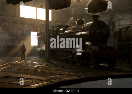 A steam locomotive, in the Evening, in the engine shed at Barrow Hill.  Sun rays shining through the window - Stock Photo