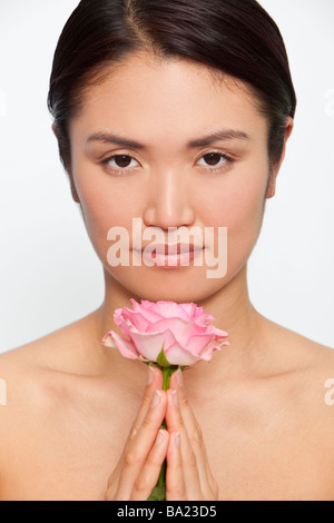 Studio shot of a beautiful young Japanese woman holding a pink rose between her clasped hands while in meditative - Stock Photo