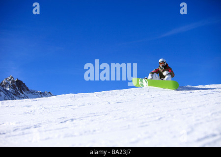 Snowboarder takes a rest on the edge of a piste in the ski resort of Tignes, Espace - Stock Photo
