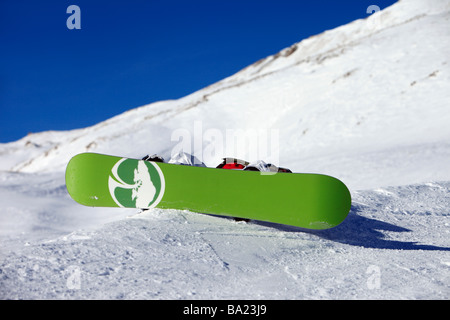 Snowboarder takes a rest on the side of a piste in the ski resort of Tignes, Espace - Stock Photo