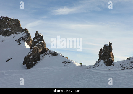 Skier climbs to the top of the Aiguille Pierce ridge for a good view in the ski resort of Tignes Le Lac, Espace - Stock Photo