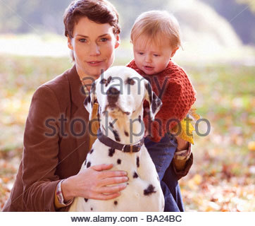 A portrait of a young mother with her baby and dog - Stock Photo