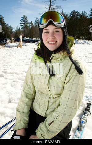 Portrait of woman skier at bottom of the hill kneeling in snow - Stock Photo