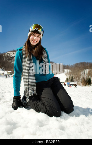 Young beautiful girl playing in snow with goggles on - Stock Photo