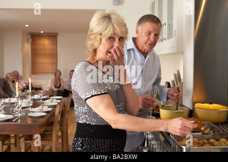 Couple Having Difficulty Cooking For A Dinner Party - Stock Photo