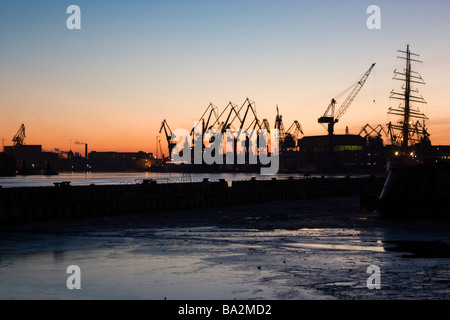 Sunset over harbour cranes in winter. - Stock Photo