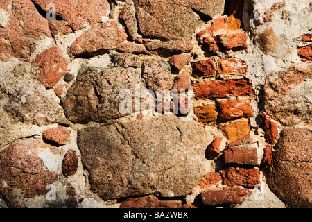 Hole in stone wall filled with bricks. - Stock Photo