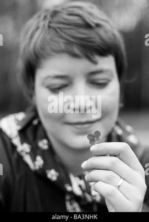 Seventies, black and white photo, people, young woman holds a four-leaf clover in her hand, wedding ring on the - Stock Photo