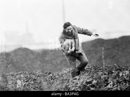 Seventies, black and white photo, people, unintentional a football was kicked in a heap, man climbs over the heap - Stock Photo