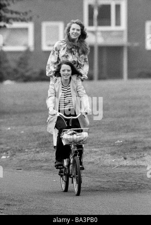 Seventies, black and white photo, people, two young girls drive on one bicycle, one girl stands on the pannier rack, - Stock Photo
