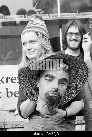 Seventies, black and white photo, humour, people, flea market, young woman presents a procuct, mans head with strawhat, - Stock Photo