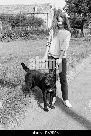 Eighties, black and white photo, human and animal, young girl walks a dog on a lead, aged 14 to 17 years, domestic - Stock Photo