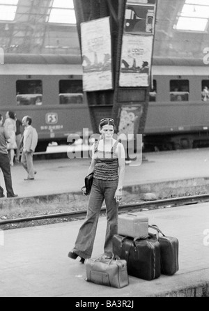 Seventies, black and white photo, railway station, Milan Central Station, young woman stands on the platform and - Stock Photo