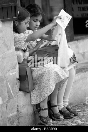 Eighties, black and white photo, people, children, two schoolgirls sit on a wall with their schoolbags, aged 9 to - Stock Photo