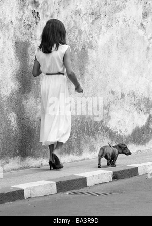 Eighties, black and white photo, human and animal, young woman walks a dachshund on a lead, aged 25 to 35 years, - Stock Photo