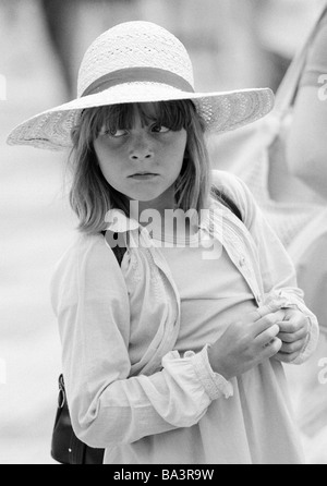 Eighties, black and white photo, people, children, little girl wearing a strawhat, portrait, aged 7 to 10 years, - Stock Photo