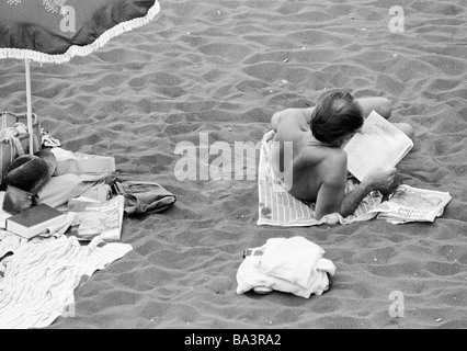 Eighties, black and white photo, holidays, tourism, man lies on the beach and reads a newspaper, Spain, Canary Islands, - Stock Photo