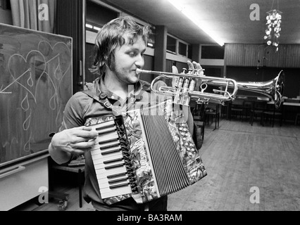Seventies, black and white photo, culture, music, humour, young man plays in a saloon trombone and accordion at - Stock Photo