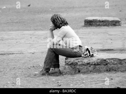Eighties, black and white photo, people, young woman sits on a wall, depression, thougtfulness, blouse, jeans trousers, - Stock Photo