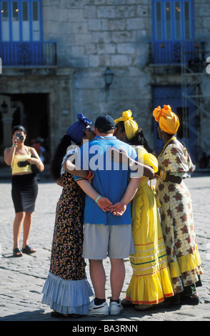 Tourist poses for photos with women in traditional Cuban dress in Old Havana Cuba - Stock Photo