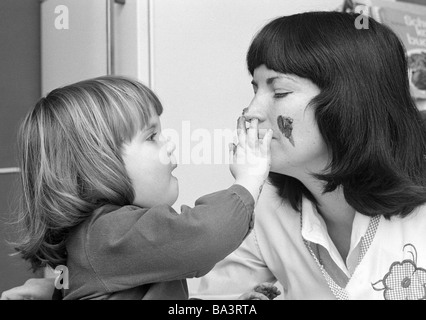 Seventies, black and white photo, people, young mother plays with the daughter, finger colouring, aged 25 to 35 - Stock Photo