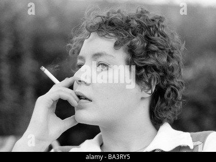 Seventies, black and white photo, people, young woman holds a cigarette in her hand, portrait, aged 23 to 28 years, - Stock Photo