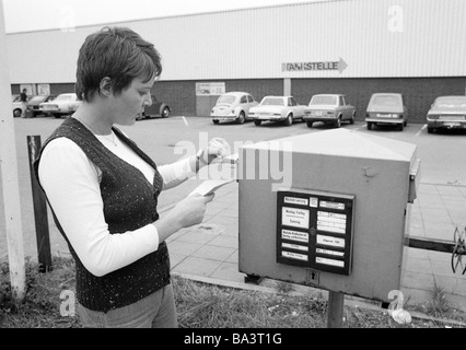 Seventies, black and white photo, people, young woman posts a letter in a letterbox, pulli, waistcoat, aged 20 to - Stock Photo