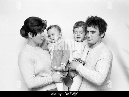 Seventies, black and white photo, people, young family with two children, mother carries daugther on her arms, father - Stock Photo