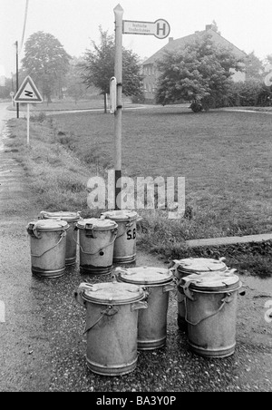 Seventies, black and white photo, humour, product photography, eight dustbins stand at a bus stop waiting for collection - Stock Photo
