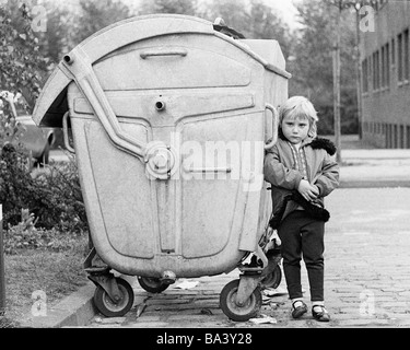 Seventies, black and white photo, people, children, little girl stands near a refuse container, aged 4 to 6 years - Stock Photo