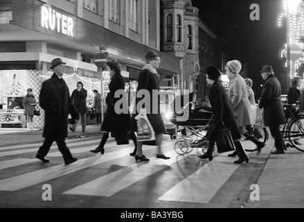 Seventies, black and white photo, people on shopping expedition, shopping street, pedestrian zone, zebra crossing, - Stock Photo