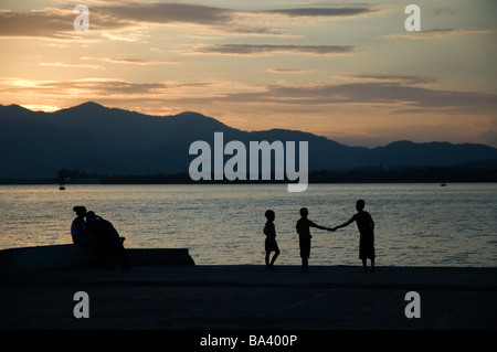 CUBA Santiago de Cuba Children playing at sunset by the port March 2009 - Stock Photo