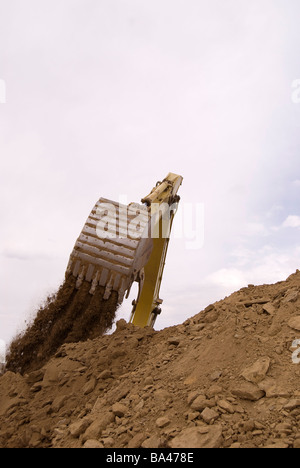 Excavator bucket dumping soil and rock onto stockpile - Stock Photo
