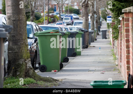 Row of black and green wheelie bins containing rubbish and recycling waste in an urban street waiting for collection - Stock Photo