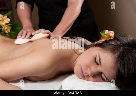 A young adult woman receives a massage with shells - Stock Photo