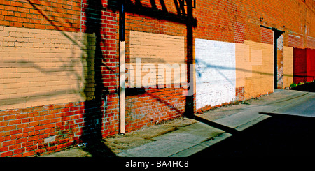 Shadows and paint squares on a brick wall in a neighborhood alley