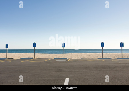 Handicap parking signs and parking spaces at beach - Stock Photo