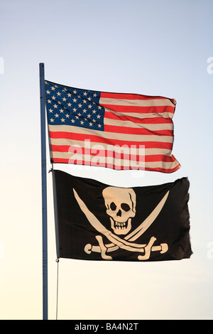 The American flag and pirate flag flying from flagpole - Stock Photo