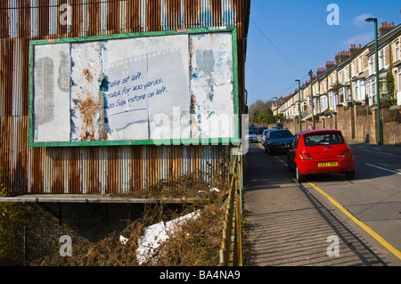 Tatty advertising billboard on end wall of house in village of Six Bells Blaenau Gwent in the South Wales Valleys - Stock Photo
