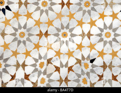 A floor made of a repeating pattern of regular shapes made from semi precious stones inlaid in white marble. - Stock Photo