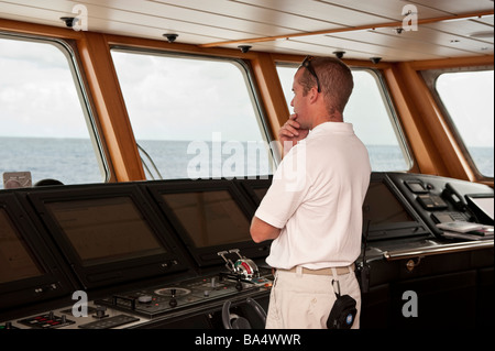 Chief Officer aboard superyacht 'Big Aron' on watch on the bridge - Stock Photo