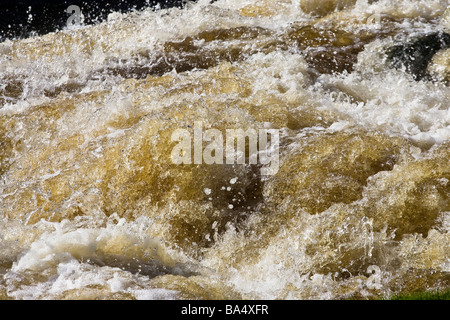 Fast flowing white water rushing down a river - Stock Photo