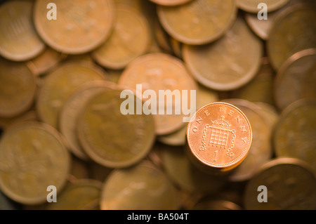 Shinny one penny against blurred 1 and 2 pence coins - Stock Photo